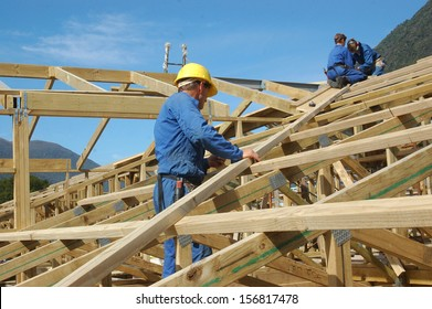 builders working on the roof of a large house