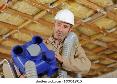 builders working on ventilation pipes