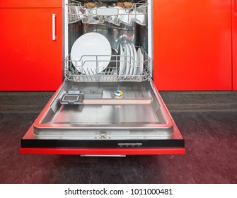 Build-in dishwasher with opened door in a red kitchen.