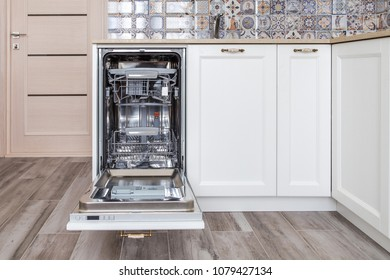 Build-in dishwasher with opened door in a white kitchen in neoclassical style with wooden front