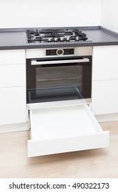 Build-in oven, hob and opened drawer below, close-up.