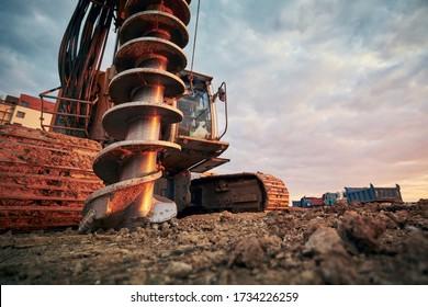 Bautätigkeit auf Baustelle. Nahaufnahme der Bohrmaschine gegen LKWs.