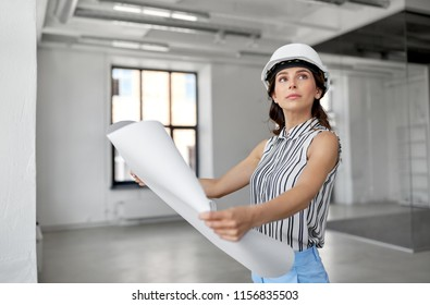 building, architecture and construction business concept - businesswoman or architect in helmet with blueprint at office room