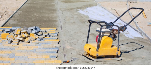 Building background - concept of laying paving slabs and pavers. Rubber hammer lie on the unfinished laying of concrete paving stones. Paver laying driveway pavement out of concrete pavement blocks