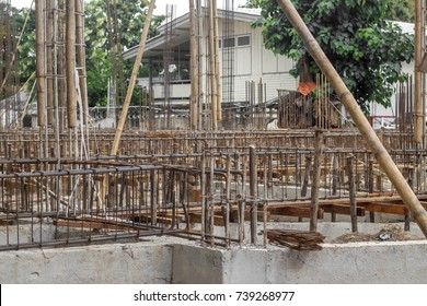 The building base construction with concrete as the floor and steel bar body with the bamboo scaffolding and big shade tree background.