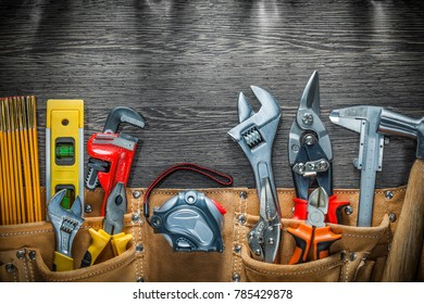 Building belt with construction tools on wooden board.