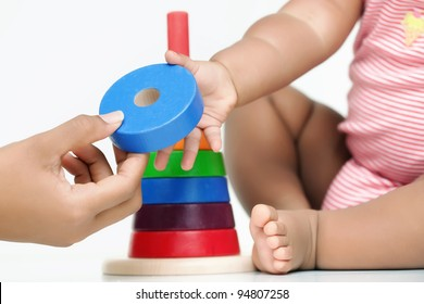 A building block being handed by an adult hand to a baby who is