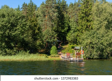 Building with a boat dock on the shore of a forest lake