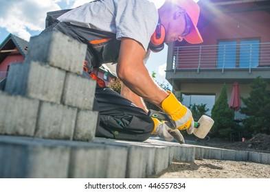 Building Brick Garden Path. Caucasian Worker Building Block Paved Hardstanding Garden Path. Brick Paving.