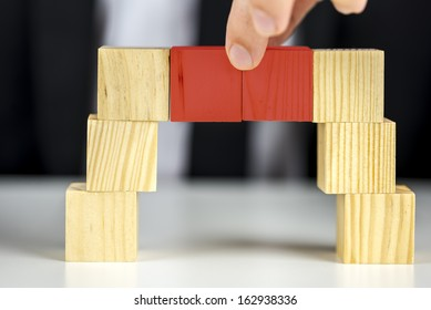 Building a business concept. Closeup of businessman making a bridge with wooden toy cubes.