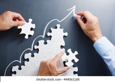 Building business. Concept image of developing growth strategy.  Working on steps shaped jigsaw puzzle. Drawing up arrow on blackboard.