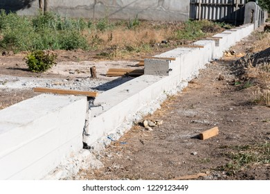 Building concrete foundation for wooden rural fence. Foundation for fence.