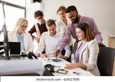 building, construction, architecture, real estate and people concept - business team with blueprint and calculator working with house project at office
