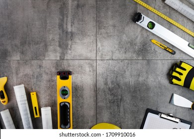 Building and construction concept. Yellow building equipment on grey tiles.