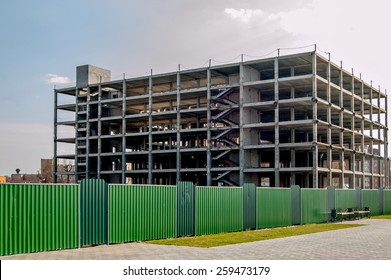 Building construction copyspace on the sky toned colorized image. Construction site. Modern building under construction and green metal fence