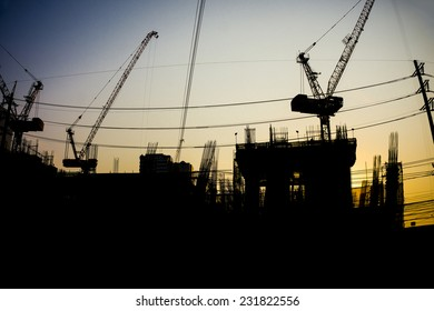 Building construction industrial with construction cranes silhouette at sunset