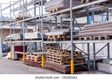 Building and construction materials for sale stored on metal shelves outdoors in a warehouse yard together with wooden pallets for loading, distribution and storage