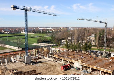 building construction site with cranes and workers