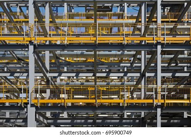 Building construction site showing steel frame with yellow safety barriers