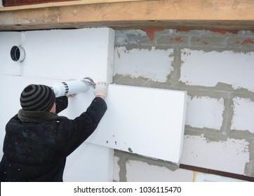 Building constructor installing rigid styrofoam insulation board for energy saving in problem area around chimney