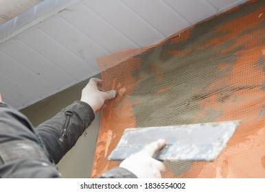 A building contractor is installing a reinforcing mesh and rendering to insulate the external wall of the house under the roofing soffit.