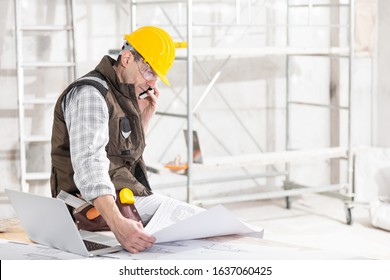 Building contractor talking on a mobile phone as he sits holding a blueprint on a workbench in a room under construction