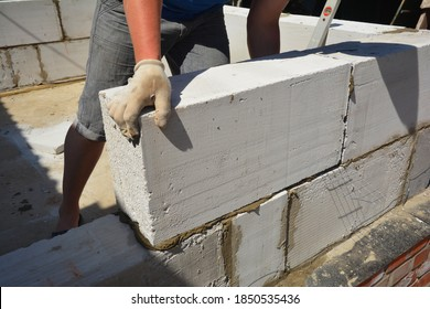 A building contractor is building a wall lying autoclaved aerated concrete (AAC) blocks over brick foundation with bitumen asphalt waterproofing membrane installed.