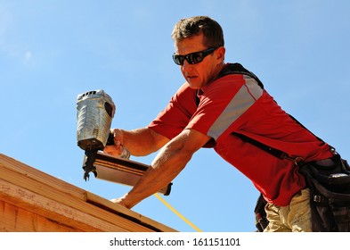 Building contractor worker with a air nail gun  nailer working on the corner of the top plate of the first floor walls on a new home construction project