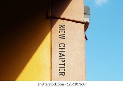 Building contrast with blue sky , text typography NEW CHAPTER ,concept of reinvent yourself and start fresh every day in different stages in life with positive mindset ,accept change as nature of life