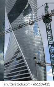 Building crane against the background of a high-rise building.