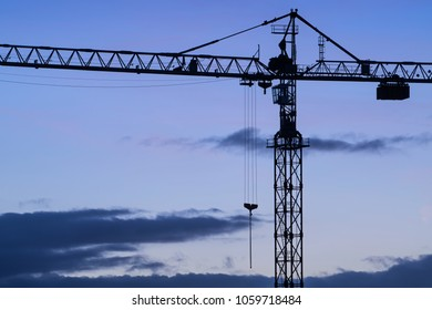 Building crane against a blue evening sky.