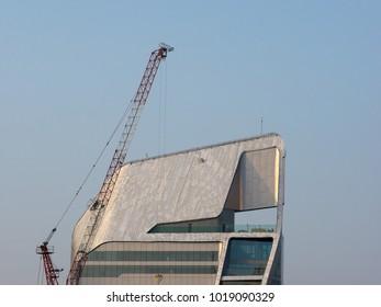 Building crane and buildings under construction against blue sky