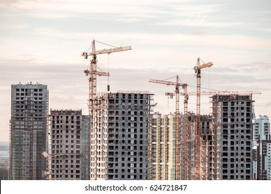 Building crane and buildings under construction against evening sky