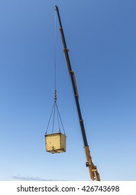 Building crane with container on steel cable against blue sky.