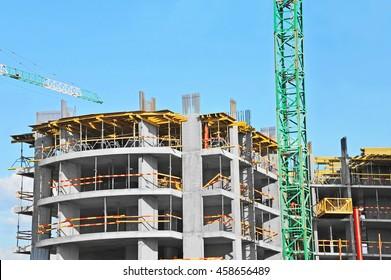 Building crane and building under construction against blue sky