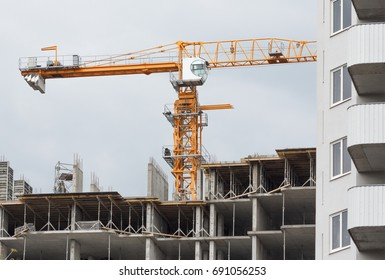 Building crane and building under construction against sky