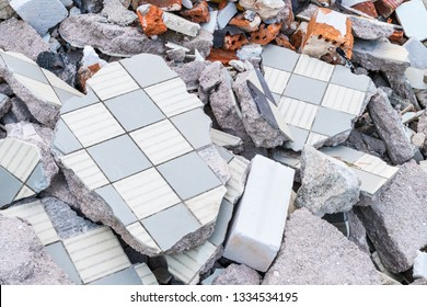 Building debris heap from broken tiles, bricks and concrete. Construction waste pieces close-up. Damaged old floor and masonry. Idea of renovation or demolition, explosion, earthquake and disaster.