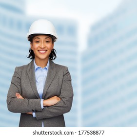 building, developing, consrtuction and architecture concept - smiling businesswoman in white helmet with crossed arms