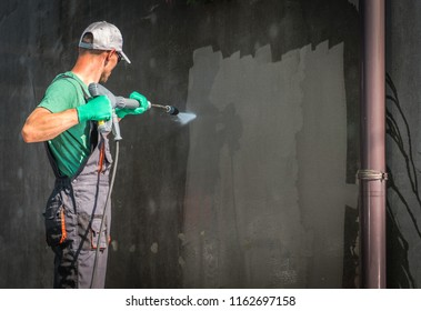 Building Elevation Pressure Washing by Worker with Power Washer. Refreshing House Outside Walls.