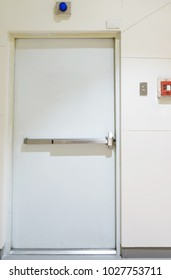 Building emergency exit with exit sign on door and fire extinguisher on the outside of a building