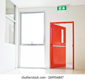 Building Emergency Exit with Exit Sign, red door opening to white