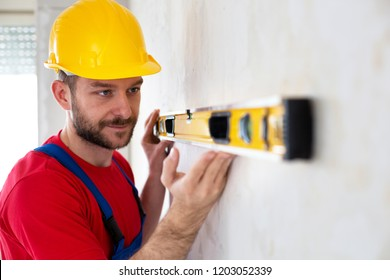 Building engineer observing  a trapped bubble  inside elongated tube of his leveling instrument
