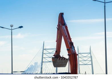 Building excavator. Construction of a large residential complex. A metal excavator bucket on the background of the bridge and the blue sky. Building sector.