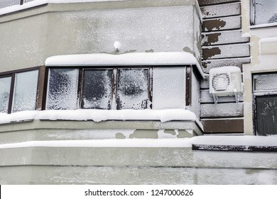 Building facade of modern high-rise apartment house covered with snow and frost after heavy windy snowstorm Snowfall and blizzard aftermath in winter. Cold snowy weather forecast