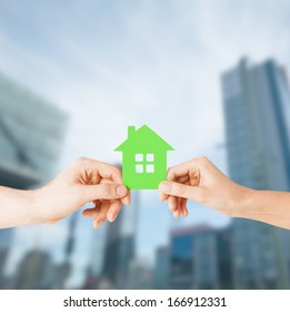 building, family and real estate concept - closeup picture of woman and man hands holding green house