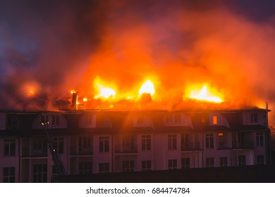 Building in fire at the night , burning fire flame with smoke on the apartment house roof.