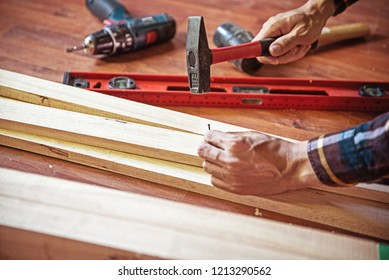 Building  with hammer while hit the nail Professional carpenter working with wood and building tools in house for renovate.