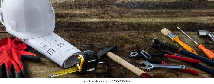 Building helmet and professional hardware tools on rustic wooden background for DIY and craftsman banner