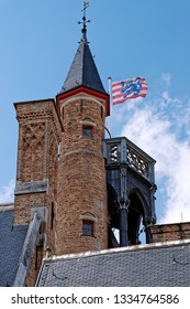 Building in the historic part of Bruges, Belgium with a sharp tower. The flag of the city of Bruges wobbles near the high tower.