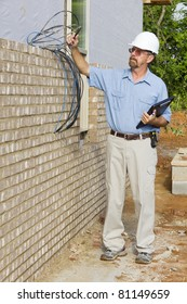 Building inspector checking electrical wires,phone lines, building framing,electrical and plumbing stub outs